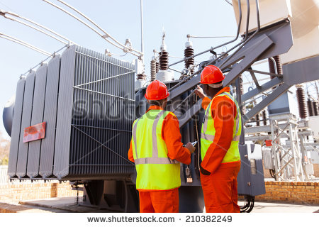 stock-photo-back-view-of-electricians-standing-next-to-a-transformer-in-electrical-power-plant-210382249